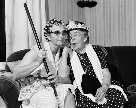 846-05648207 © ClassicStock / Masterfile Model Release: Yes Property Release: No 1950s - 1960s TWO ELDERLY WOMEN CHARACTERS GOSSIPING ONE WOMAN WITH HAIR CURLERS OTHER WITH HAT
